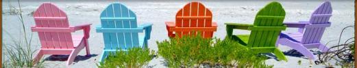 Bunte Holzstühle am Strand
